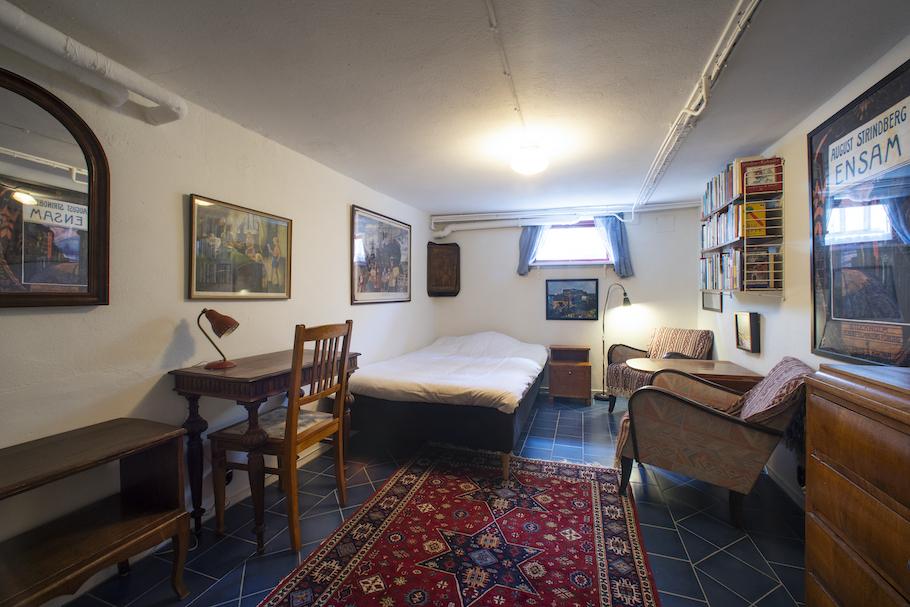Rum med litet skrivbord, säng, litet fönster, sängbord, vägghylla med böcker, fåtöljgrupp och byrå.