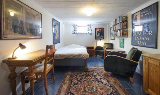 Rum med skrivbord, säng, litet fönster, sängbord, vägghylla med böcker, fåtöljgrupp och ett skåp.