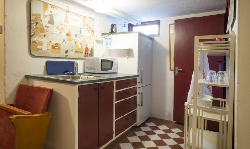 Miniköket en våning ner med diskho, mikro, kyl/frys samt en hylla med porslin och glas.