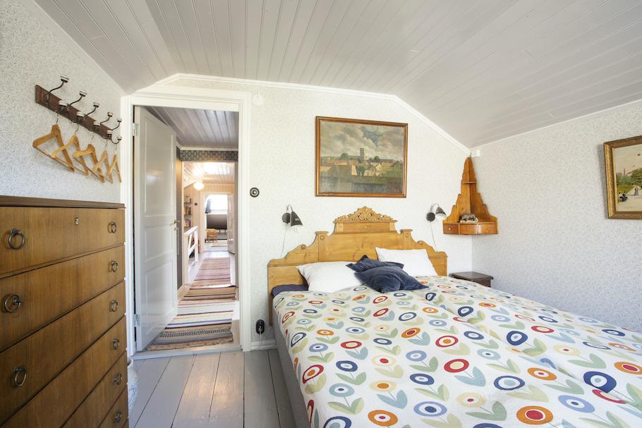 Rummet sett från fönstersidan med säng, byrå och klädhängare.