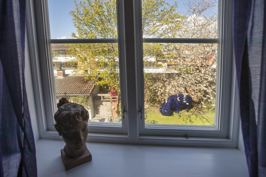 Utsikten från fönstret mot trädgården med ett magnoliaträd och en stor blå flodhäst.