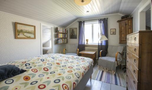 Rummet sett från dörren med säng, fåtöljer, bord och byrå.