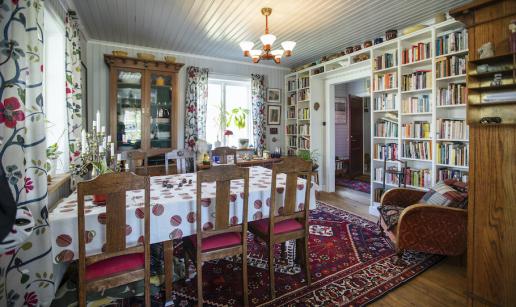 Frukostrum med matsalsmöbel, vitrinskåp, fåtölj samt bokhylla med  böcker och prydnadsföremål.