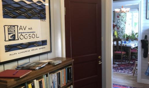 Gästentréns hall med bokhylla och tavla föreställande ett bokomslag.