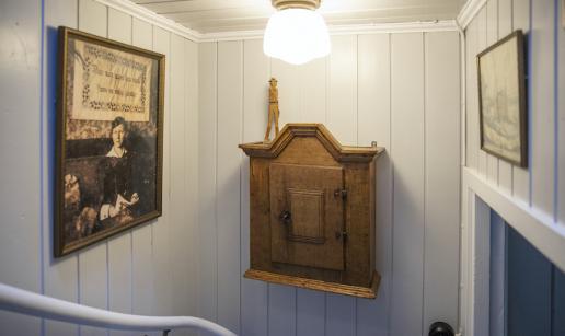 Ett gammalt porträttfotografi och ett väggskåp i trä i trappan upp till andra våning.