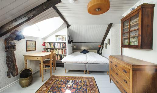 Ett rum med snedtak och ljusinsläpp från takkupa. En krokodil av trä på väggen, ett bord, bokhylla, två sängar, ett väggskåp och en byrå.
