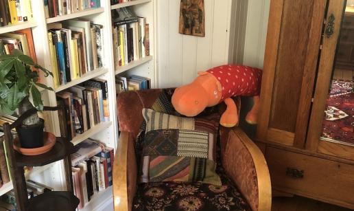 Läshörna med fåtölj och bokhylla i frukostrummet.