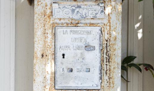 En patinerad fransk postlåda på en husvägg.