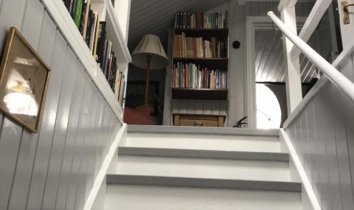 Trappan upp till andra våning med ljust grå panel och bokhyllor.