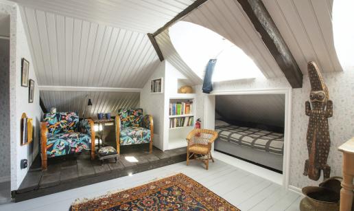 Ett rum med snedtak och ljusinsläpp från takkupa. Två fåtöljer, liten sovalkov, krokodil av trä på väggen.