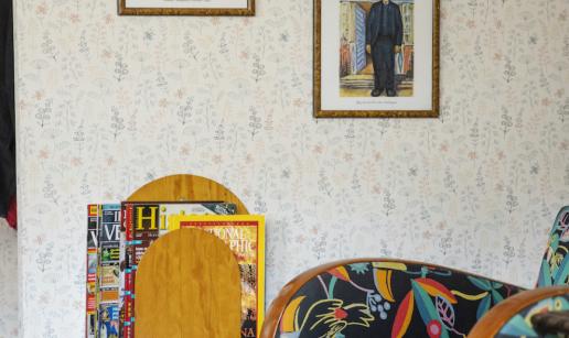 En vägg med blommig tapet, två målningar och ett tidningsställ.