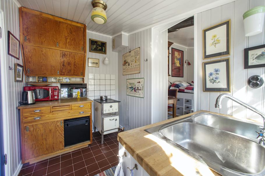 Stugans kök med lådor och skåp i retrostil. En gammal spis/ugn, mikro, diskho.