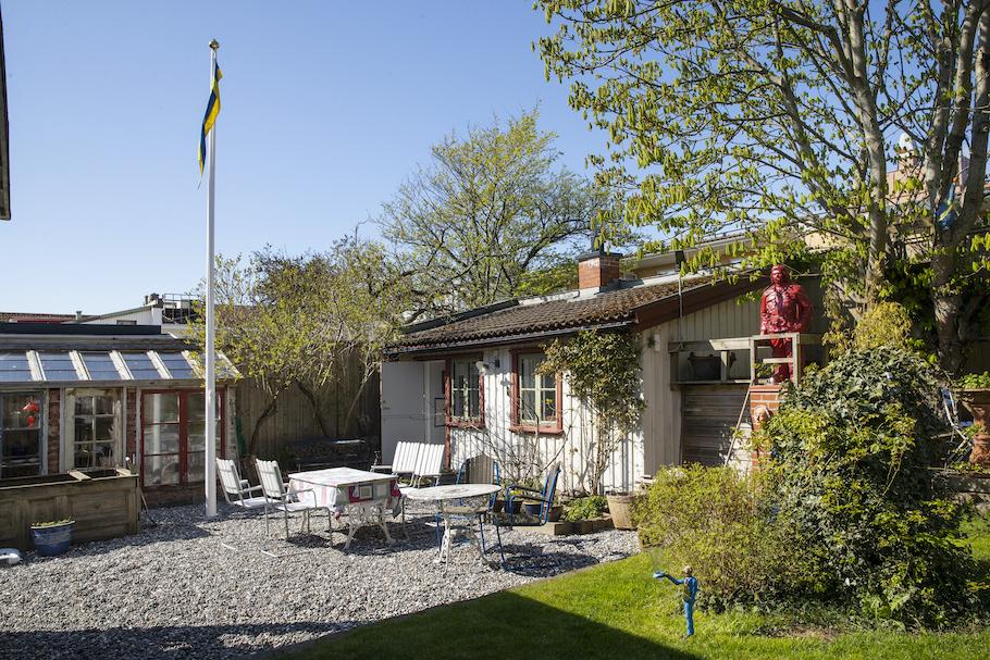 Stugan sedd från trädgården med växthus och flaggstång till vänster, sittgrupp på grusad uteplats framför stugan.
