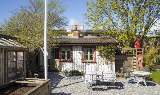 Stugan utvändigt med växthus och flaggstång till vänster, sittgrupp på grusad uteplats framför stugan.