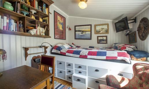Rum med matbord, vägghylla, säng, vägghängd TV och fåtölj.