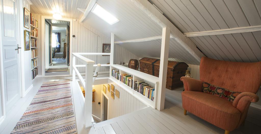 Övre hall med trappavsats, fåtölj, kista och böcker.