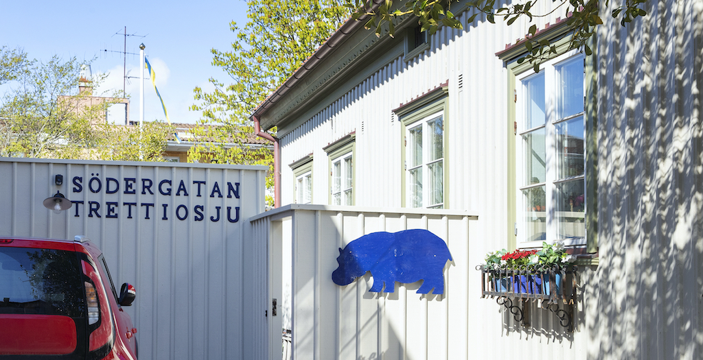 Entré till Södergatan 37. Ett gråvitt plank med gatunummer och en blå skylt i form av en flodhäst. En husvägg med fyra fönster.
