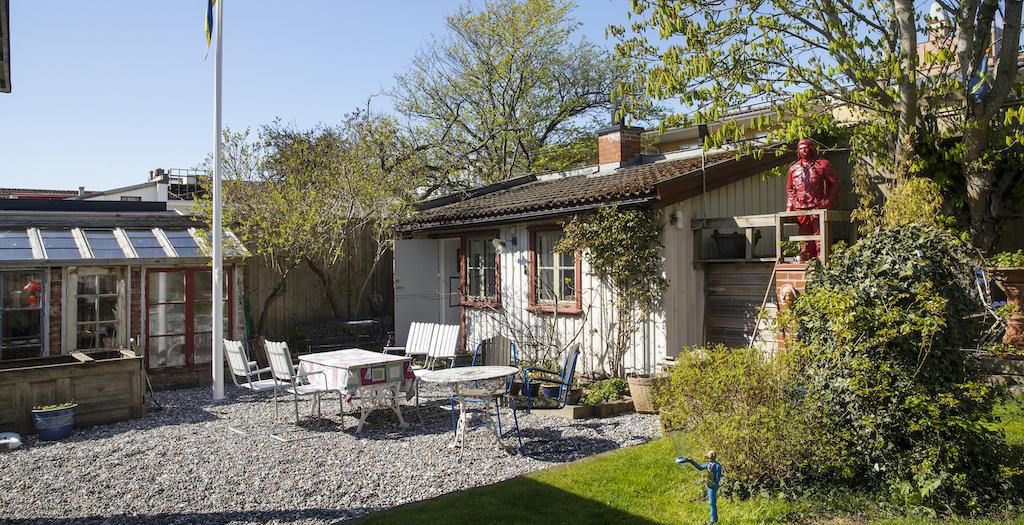 Trädgård med stuga, sittgrupp och växthus.