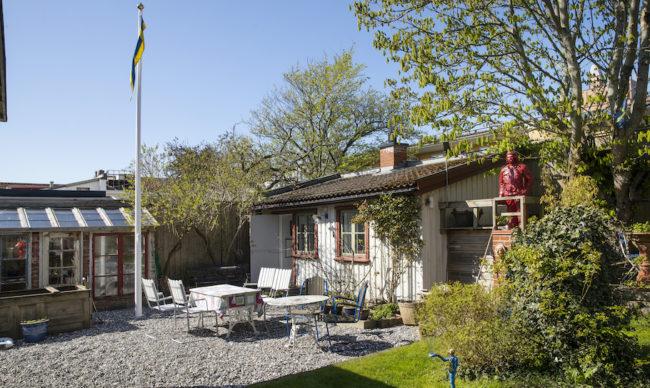 Litet växthus och en stuga i trädgården.