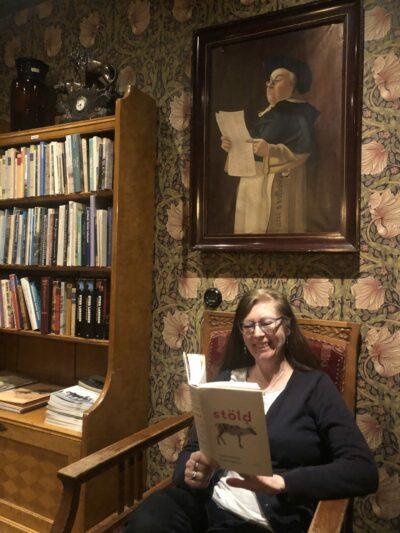 Elisabeth sitter i en fåtölj i Hotell Gästis foajé och läser boken Stöld. Till vänster om henne finns en bokhylla och på väggen ovanför henne hänger en tavla.