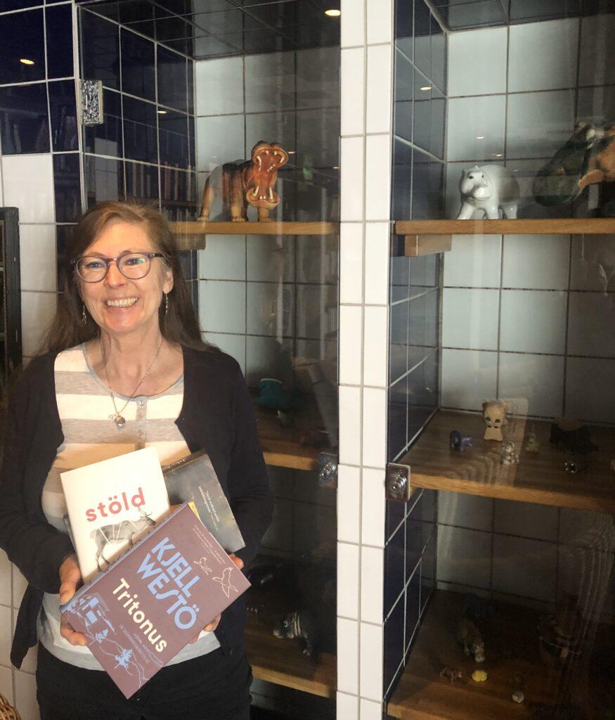 Elisabeth håller i en trave böcker framför en glasmonter med flodhästar i Leninbadet.